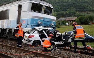 Les pompiers s'affairent le 10 août 2009 à Saint-Jean-de-la-Porte, après qu'un train-corail a percuté une voiture sur un passage à niveau.