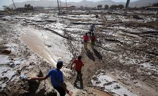 Des habitants cheminent sur une route inondée à Diego de Almagro, à 1.000 km au nord de Santiago du Chili, le 29 mars 2015.
