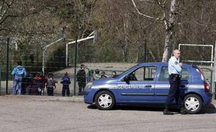 Des gendarmes devant l'école de Villefontaine où exerçait le directeur d'école soupçonné de viols le 24 mars 2015