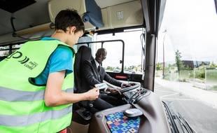 Un élève monte dans un car scolaire avec le nouveau gilet vert de la région Pays-de-la-Loire.