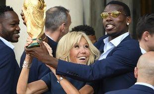 Brigitte Macron et Paul Pogba soulèvent la Coupe du monde de football, le 16 juillet 2018 à l'Elysée.
