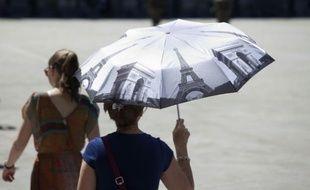 Une femme se protège du soleil à Paris, le 30 juin 2015