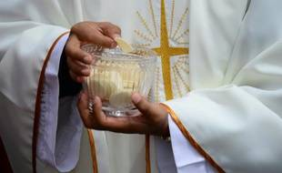 Le 7 juillet 2015. Un prêtre donnant la communion (Illustration).