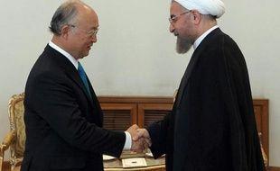 Photo fournie par la présidence iranienne montrant le président iranien Hassan Rohani (d) serrant la main du patron de l'Agence internationale de l'énergie atomique (AIEA,)Yukiya Amano, le 17 aoput 2014 à Téhéran