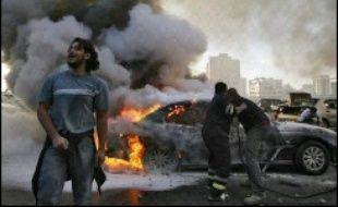 Des Libanais tentent d'éteindre une voiture incendiée, le 25 janvier 2007 à Beyrouth, théâtre d'affrontements depuis plusieurs jours
