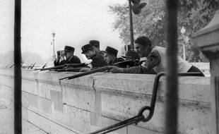 Photo prise en août 1944 de policiers et d'un membre des FFI (Forces Françaises de l'Intérieur) surveillant les quais de la Seine, près de la préfecture lors de la libération de Paris.