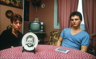 Christine et Jean-Marie Villemin, les parents du petit Grégory, 4 ans, retrouvé noyé le 16 octobre 1984, pieds et poings liés dans la Vologne, sont assis, le 23 novembre 1984, autour de la table de leur salle-à-manger sur laquelle est posée une assiette à l'effigie de leur enfant.
