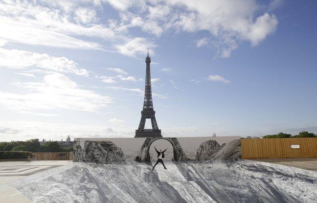 Un homme saute devant le trompe-l'oeil créé par l'artiste JR devant la Tour Eiffel.