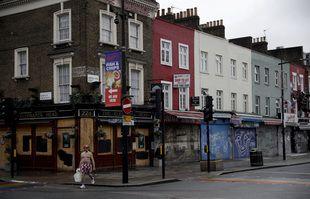 Un homme passe devant des magasins temporairement fermés et un pub à Camden Town, un quartier de Londres généralement animé de touristes et de visiteurs de son marché, le mardi 12 janvier 2021.