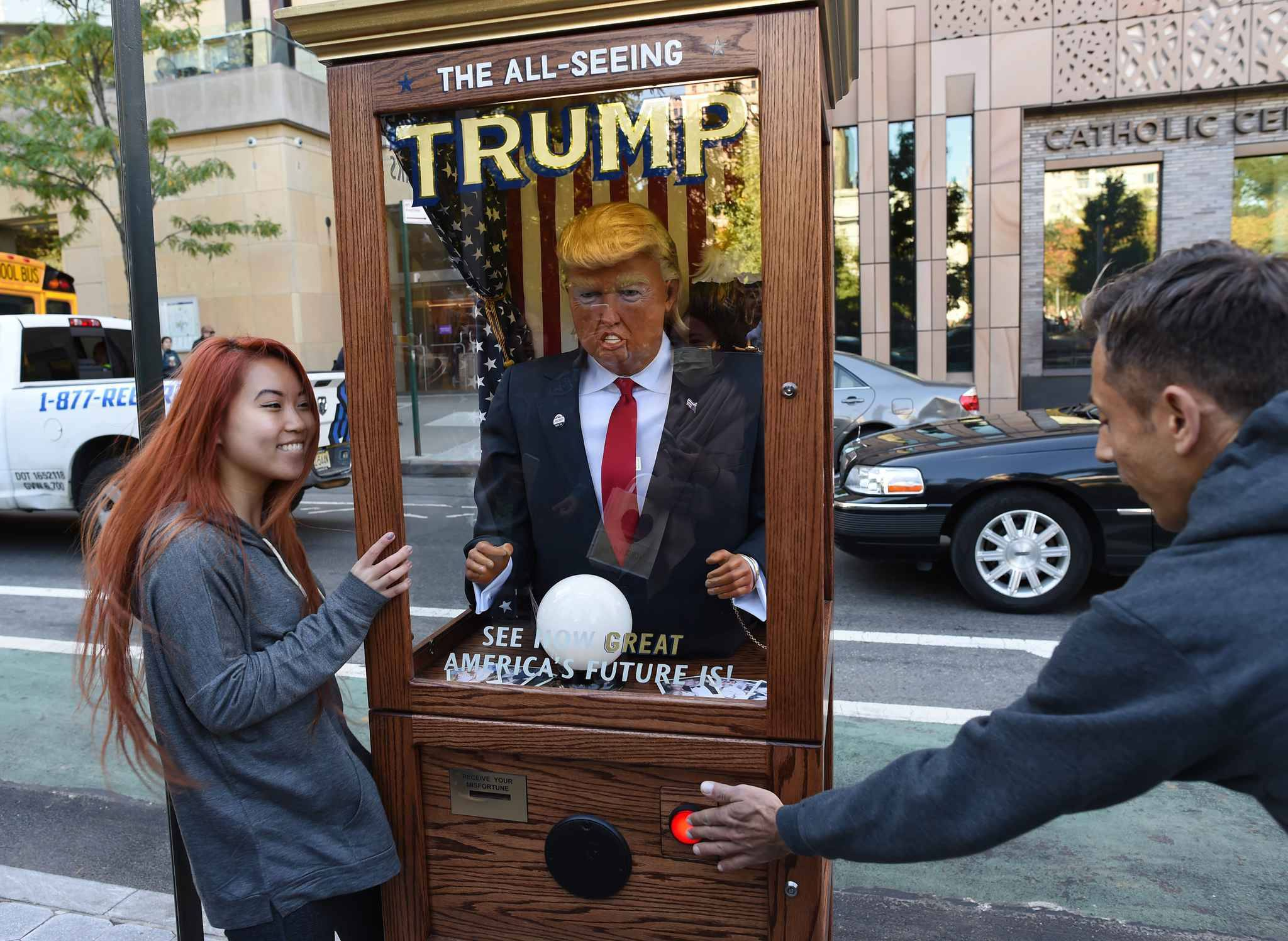 "A fortune-telling fairground attraction bearing the likeness of US Republican presidential candidate Donald Trump stands at Washington Square Park in New York on October 14, 2016.  New York has been both tickled and repelled by a fortune-telling, Trump-in-a-box mocking his offense-dishing campaign for president. ""Look into my crystal ball and see America's future,"" intones the animatronic mannequin in the Republican nominee's voice.  / AFP PHOTO / TIMOTHY A. CLARY"