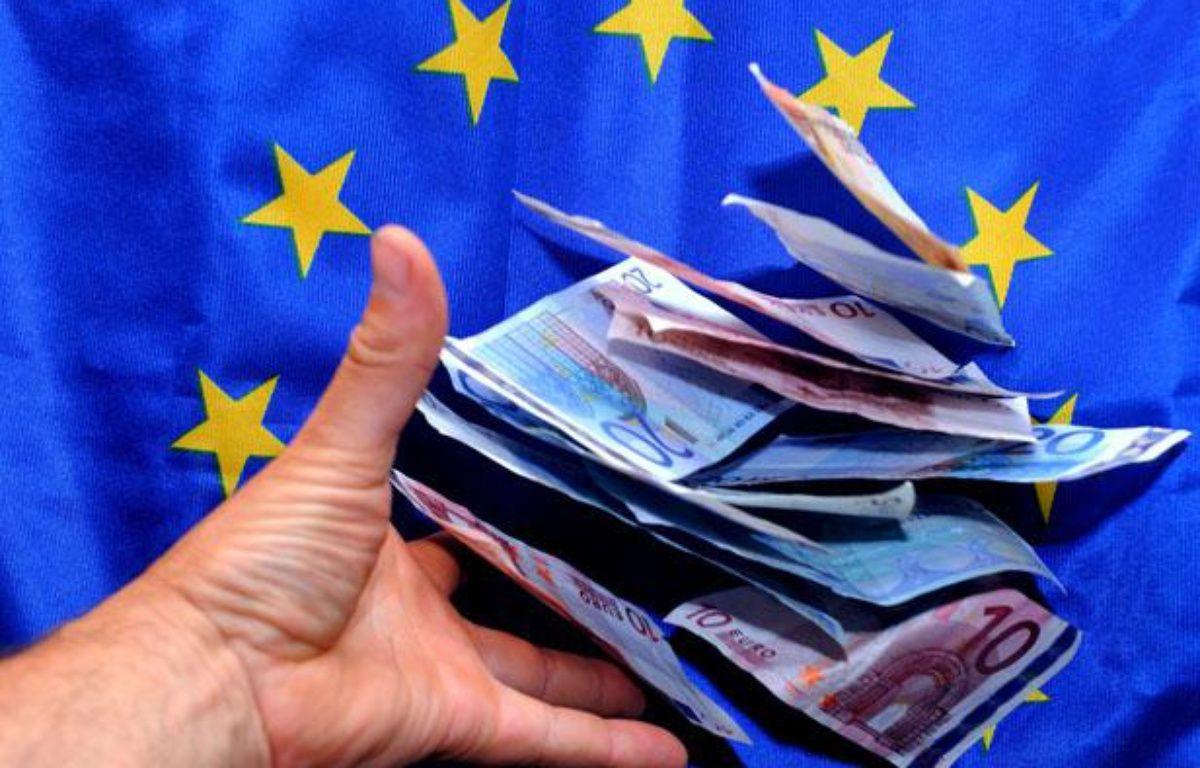 Une personne place des billets en euro devant un drapeau européen. – PHILIPPE HUGUEN / AFP