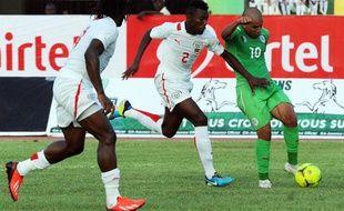 Le joueur algérien Sofiane Faghouli (à droite) lutte pour le ballon avec le joueur burkinabé Steeve Yago lors d'un match opposant leurs deux pays le 12 octobre 2013 à Ouagadougou.