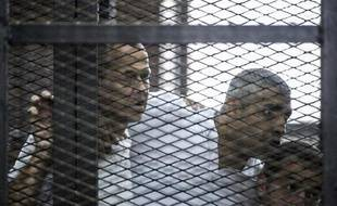 Les journalistes australien Peter Greste (g), canado-égyptien Fadel Fahmi (c) et égyptien Baher Mohamed écoutent la sentence prononcée contre eux depuis le box des accusés au tribunal de police du Caire, le 23 juin 2014