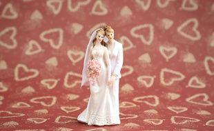 Deux figurines de mariées enlacées. Illustration.