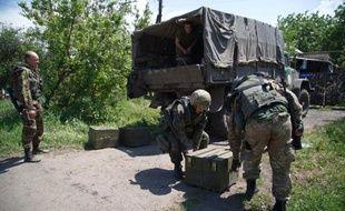Des militaires ukrainiens déchargent des munitions dans la localité de Mariinka, à l'est de Donetsk (est), le 5 juin 2015, qui a fait l'objet d'une offensive des séparatistes pro-russes