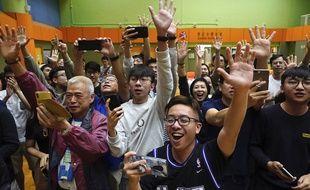 Des soutiens d'un candidat pro-démocratie célèbrent leur victoire, à Hong Kong, dans la matinée du 25 novembre 2019.