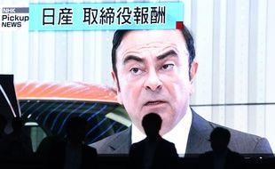 Un homme passe devant un écran qui retransmet les informations sur l'arrestation de Carlos Ghosn à Tokyo.