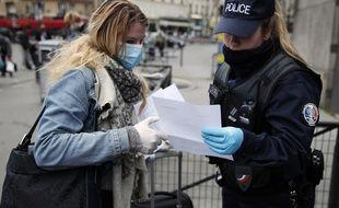 Une policière contrôle une passante devant le gare Montparnasse à Paris, le 21 mars 2020.