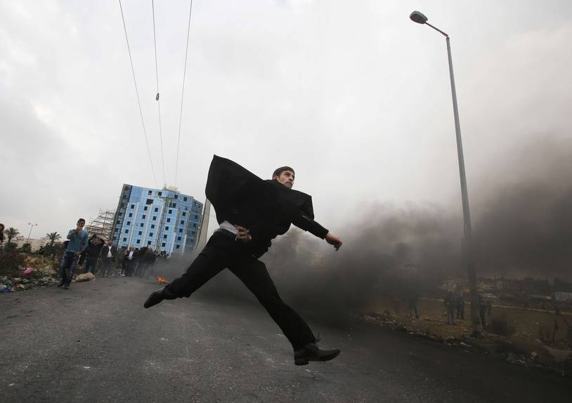 A Palestinian lawyer hurls stones towards Israeli troops during clashes following protest against U.S. President Donald Trump's decision to recognize Jerusalem as the capital of Israel, in the West Bank city of Ramallah, Wednesday, Dec.13, 2017.