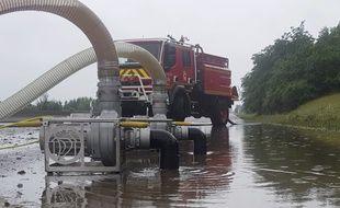 Des pompiers pompent l'eau qui inonde l'autoroute A13 entre Orgeval et Villennes-sur-Seine dans les Yvelines, le 12 juin 2018.