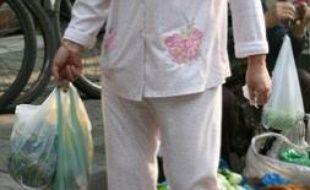 Une femme fait ses courses en pyjama.