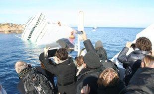 Des journalistes photographient l'épave duCosta Concordia, le 20 janvier 2012.
