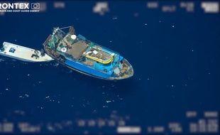 Le bateau, suivi d'un canot de fortune où sont débarqués les migrants.