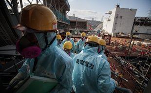 Les employés de TEPCO se tiennent devant le réacteur numéro 3 de la centrale de Fukushima Daiichi, le 31 janvier 2018.