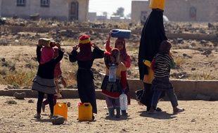 Une femme yéménite et ses enfants portent des jerrycans d'eau à Sanaa, le 14 novembre 2016.