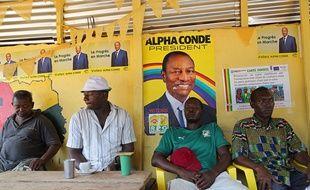 Des Guinéens attablés dans un restaurant de la capitale Conakry sous des affiches du président sortant Alpha Condé, le 17 octobre 2015.