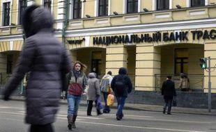 Des piétons passent devant le siège du Trust Bank à Moscou le 22 décembre 2014