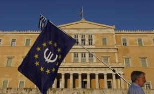 Un homme avec un drapeau européen frappé du symbole de l'euro, place du Parlement à Athènes (Grèce), le 9 juillet 2015.
