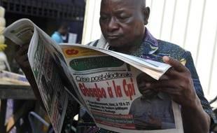 Un homme lit un journal annonçant le transfert de Laurent Gbagbo à la Cour pénale internationale de La Haye, dans le quartier d'Abobo, à Abidjan, le 30 novembre 2011.