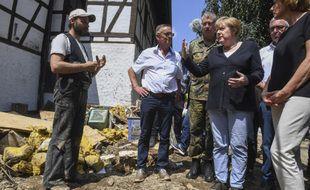 La chancelière allemande Angela Merkel et le gouverneur de l'État allemand de Rhénanie-Palatinat, Malu Dreyer, discutent avec des habitants de Schuld, dans l'ouest de l'Allemagne, dimanche 18 juillet 2021 lors de leur visite des zones ravagées par les inondations pour évaluer les dégâts et rencontrer les survivants.