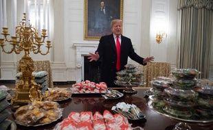 Dans la salle à manger de la Maison Blanche, le président Donald Trump s'exprime lors d'une cérémonie en l'honneur des  joueurs de l'équipe de football des Clemson Tigers. Des plats de Fast-food payés par le chef d'Etat américain sont entreposés.