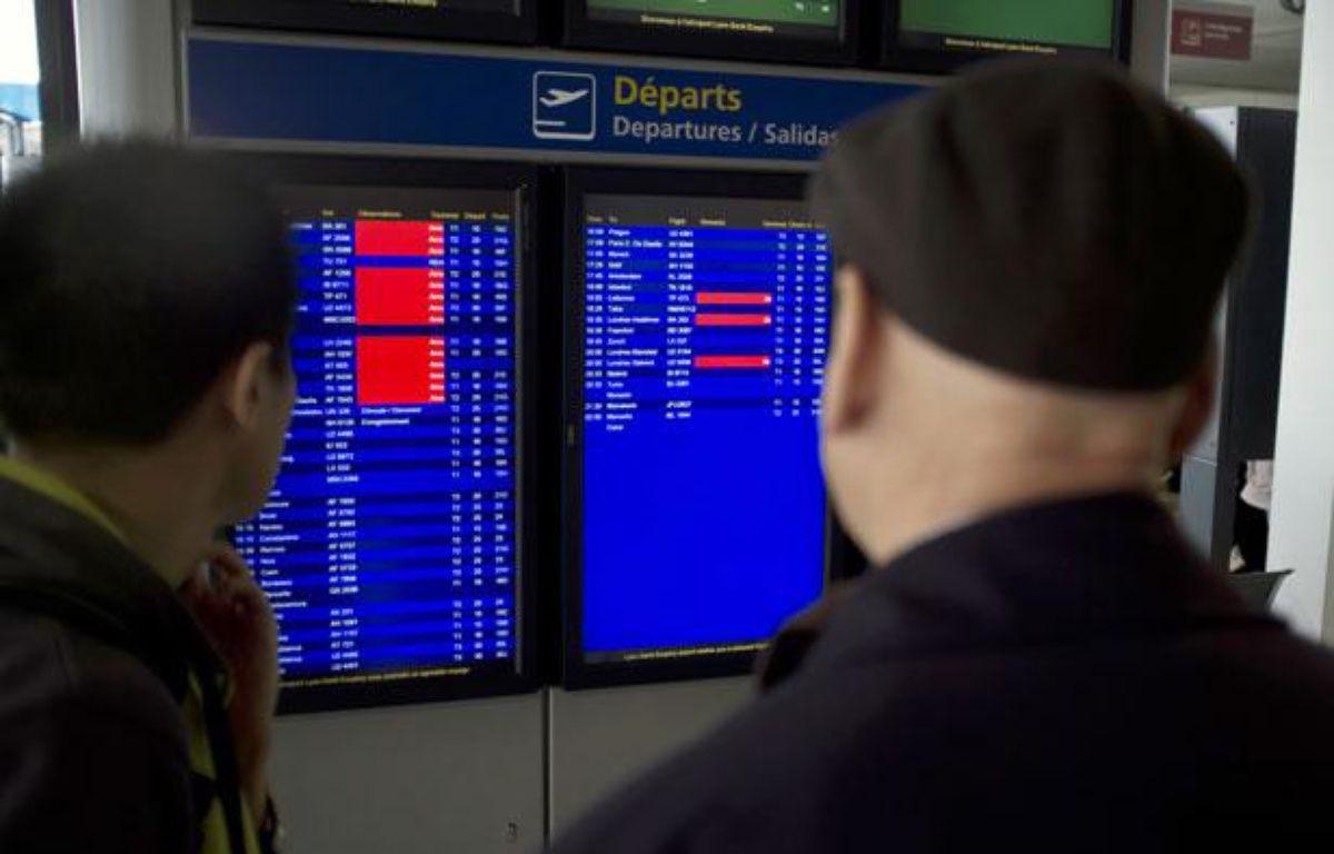 Des passagers regardent la liste des vols à l'aéroport de Lyon Saint-Exupery, le 17 décembre 2011. – AFP PHOTO / JEAN-PHILIPPE KSIAZEK