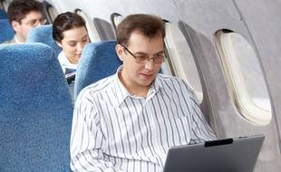 Un homme utilise son ordinateur en avion (illustration).