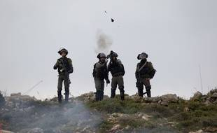 Des soldats israéliens lancent des grenades lacrymogènes à la frontière entre Gaza et Israël, vendredi 30 mars.