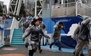 Des visiteurs d'un parc d'attraction participent à la simulation d'une frappe de missile le 22 janvier 2018 à Tokyo.