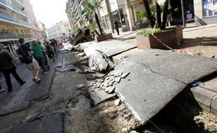 Des personnes marchent dans une rue dévastée par les intempéries à Cannes le 4 octobre 2015