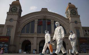 Des hommes en combinaison de protection passent devant la gare de Hankou à la veille de la reprise du trafic à Wuhan, dans la province du Hubei, dans le centre de la Chine, le 7 avril 2020.