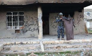 Un membre des forces kurdes tient un vêtement ayant appartenu à un djihadiste de Daesh à Kahrez, à 55 km du Mont SInjar, en Irak, le 18 décembre 2014.