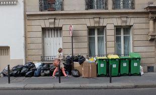 Une personne traverse devant un alignement de poubelles bien remplies le 11 juin 2016 en plein grève des éboueurs (Photo illustration).
