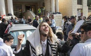 Un juif ultra-orthodoxe prie devant l'entrée de la synagogue à Jérusalem le 18 novembre 2014, quelques heures après une attaque qui a fait quatre morts parmi les fidèles