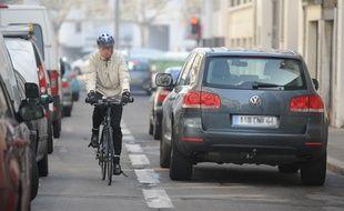 Illustration d'un vélo et d'une voiture, dans une rue à Nantes