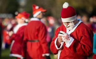 Un homme déguisé en père Noël utilise un smartphone.