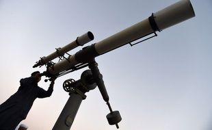 Un homme observe le ciel dans son télescope (image d'illustration).