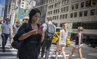 Une passante consulte son téléphone en traversant la rue à New York.
