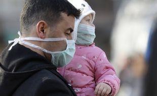 Un homme tient un enfant dans les bras, tous les deux portant un masque pour se protéger de l'épidémie de coronavirus