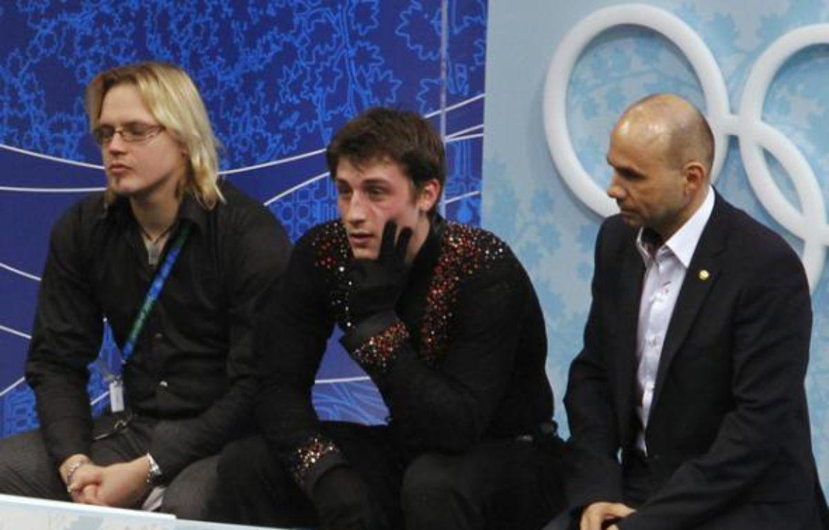 Le patineur français Brian Joubert (au centre), avec ses entraîneurs dont Laurent Depouilly (à droite) après son programme court sur la patinoire des Jeux de Vancouver, le 16 février 2010. – REUTERS